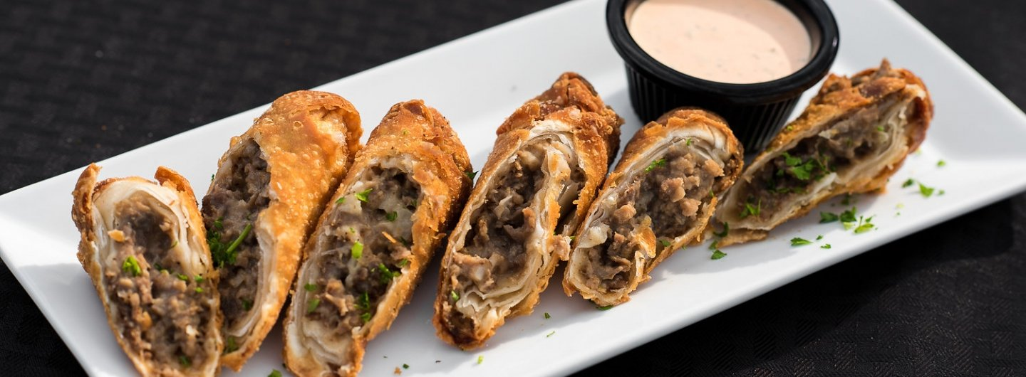 philly cheese steak spring rolls with a light orange dipping sauce