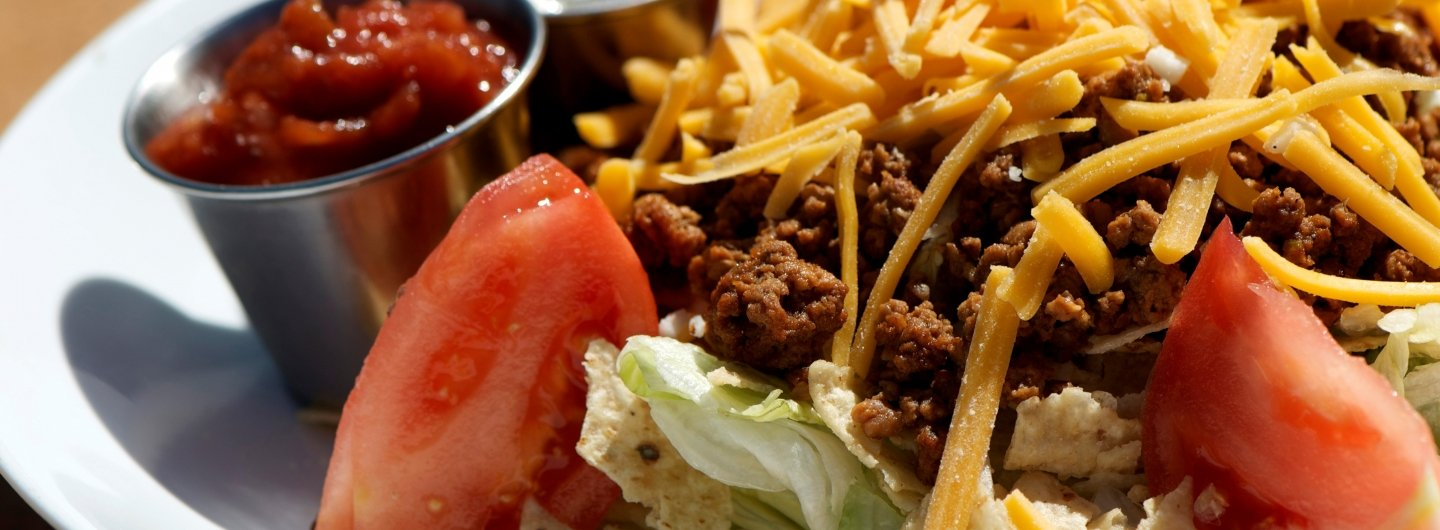 taco salad with cheese, lettuce and tomatoes