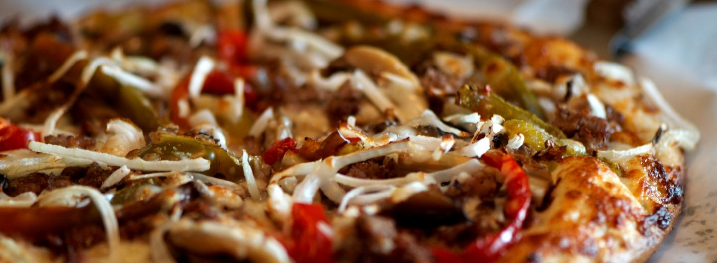 cheese pizza topped with steak, green and red peppers and onions